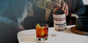 A man with a gold watch on his wrist holds a bottle of Russell's Reserve 10 Years Old Bourbon, next to a cocktail