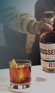 A man holders a Russell's Reserve bottle next to a cocktail