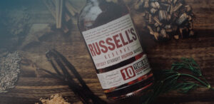 Russell's Reserve Single Barrel bottle on wood table with ingredients