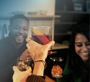A group of friends engaged in a cheers with Russell's Reserve-based cocktails